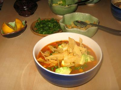 Vegan/Vegetarian Tortilla Soup in blue bowl with toppings in bowls behind it